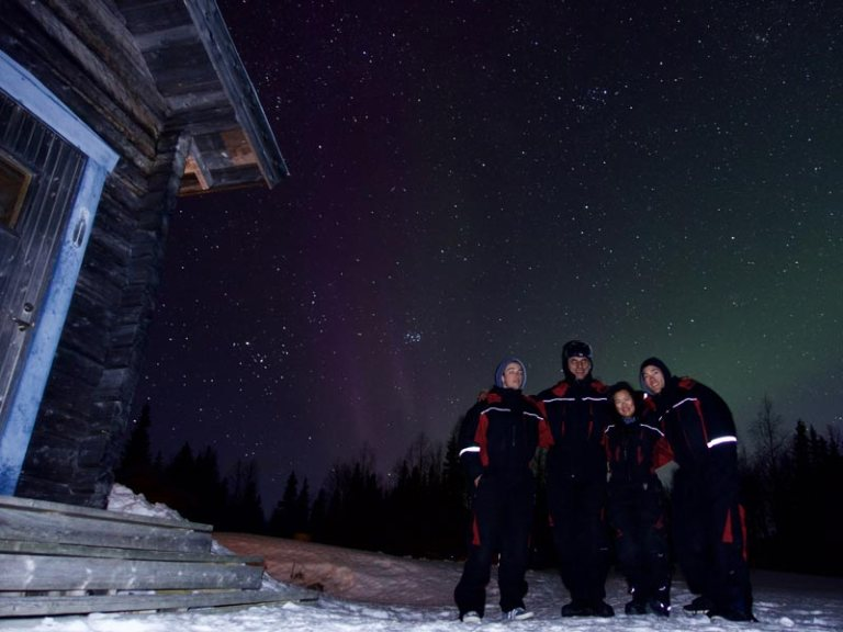 Group of dogsled guests watching the Aurora