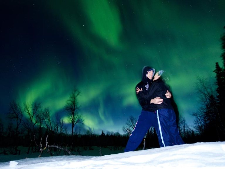 Couple with Northern Lights display behind
